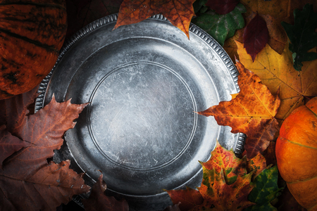 tinge: Old  round metal plate with autumn leaves and pumpkins