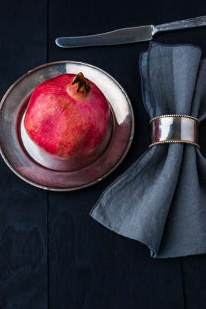 dinnerware: Pomegranate with old vintage dinnerware Stock Photo