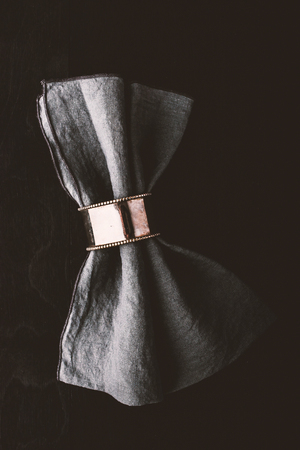 napkin ring: Grey napkin in the vintage metal ring on the black wooden table Stock Photo