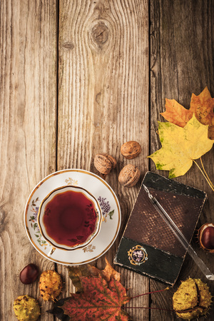 tinge: Autumnal still life with  gift of nature , vintage notebook and tea with film filter effect  background
