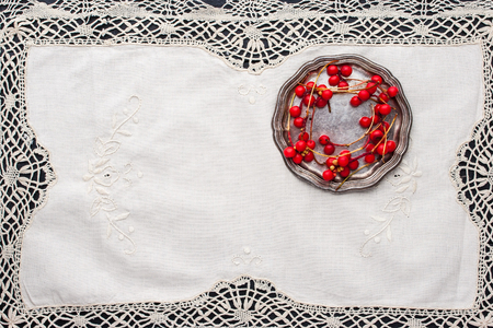 Sprig of red berries  on the  old vintage  lace napkin Stock Photo