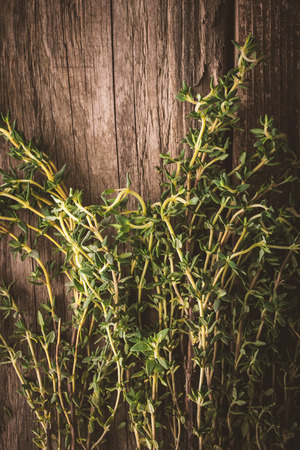 piquancy: Thyme on the old wooden board vertical