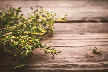 piquancy: Bundle of thyme on the old wooden board Stock Photo