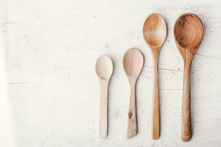 Wooden spoons on the white table top view