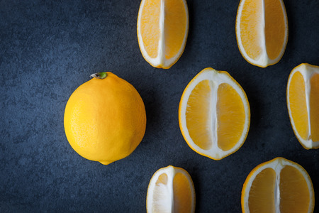 lemon slices: Yellow lemons on a blue stone table horizontal