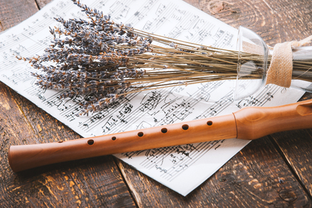old sheet music: Flute with notes and lavender on the wooden table horizontal