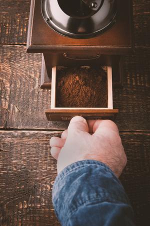 hombre tomando cafe: Molino de caf� con la mano en la mesa de madera verticales Foto de archivo