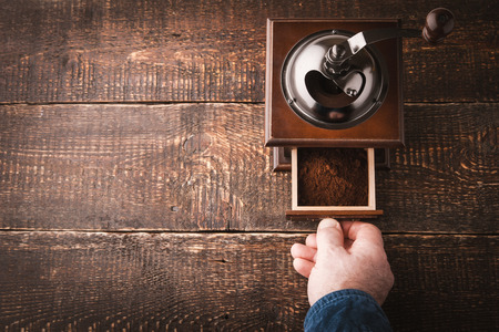 man drinking coffee: Coffee mill with hand on the wooden table horizontal