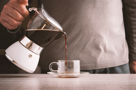 and the horizontal man: Man pouring coffee into a glass cup horizontal