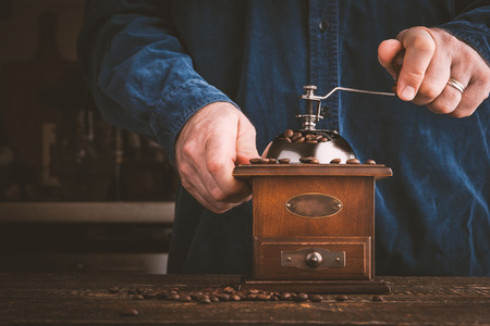 and the horizontal man: Man grinding coffee in coffee mill horizontal