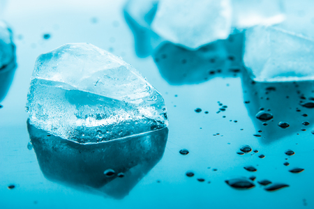 refrigerate: Piece of ice on the blue background  horizontal