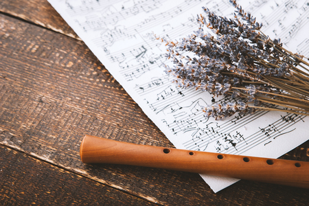 old sheet music: Flute with notes and lavender on the wooden table