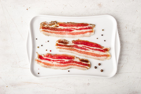 Streaky bacon with black pepper on the white plate top view
