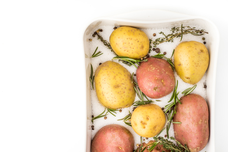 backing: Raw potatoes with spices and herbs in the backing dish