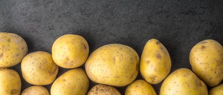 wide screen: Raw potatoes on the dark stone table wide screen