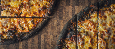 wide screen: Sliced dough black pizza on the wooden table wide screen