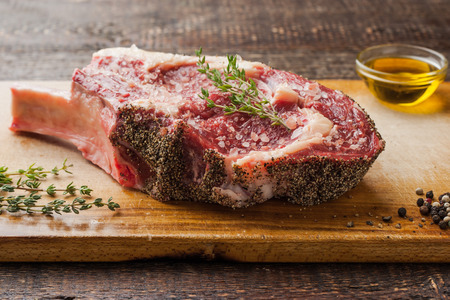 not ready: Tomahawk steak on the bone with thyme on cutting board horizontal