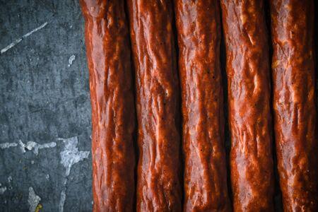 blue metallic background: Several smoked sausages on a blue metallic background horizontal Stock Photo