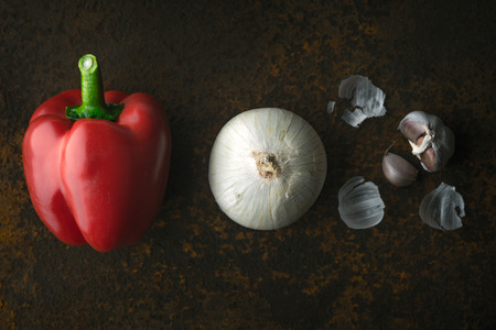 cebolla blanca: Red pepper, white onion and garlic on a metal background horizontal