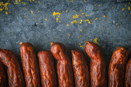 blue metallic background: Many smoked sausages on a blue metallic background horizontal