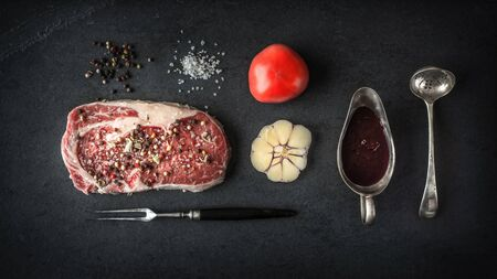 schist: Piece of ribeye steak marble, tomato and garlic on blue schist horizontal Stock Photo