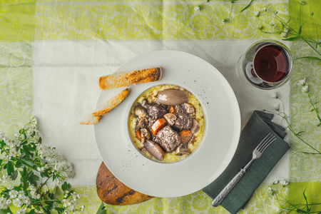 flowers horizontal: Beef bourguignon in a ceramic plate on a tablecloth and white flowers horizontal Stock Photo