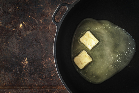 Pieces of butter in the hot pan, top view Stock Photo