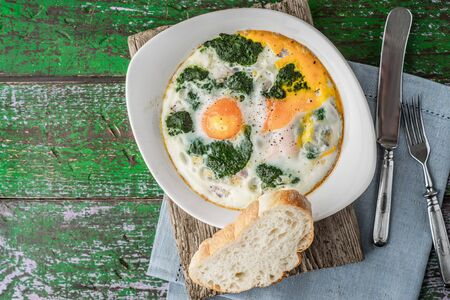 pureed: Florentine eggs with pureed spinach on the wooden table Stock Photo