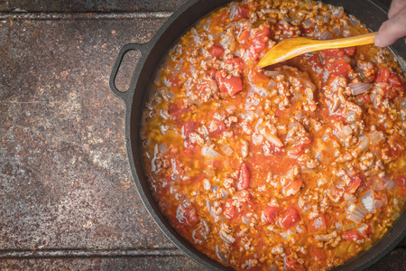 stew pan: Stew meat with onion and tomatoes in the pan, top view