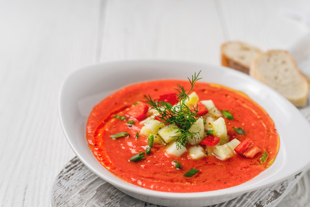 gaspacho: Vegetable soup gazpacho, stand, bread slices on white boards horizontal Stock Photo