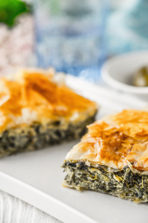 fillo: Greek pie spanakopita on the white plate with blurred accessorizes
