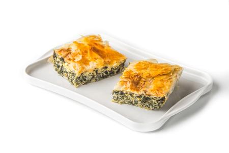 fillo: Piece of Greek pie spanakopita on the white plate on the white background