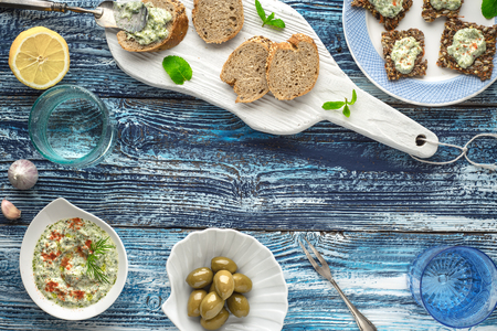 accessorize: Bread with tzatziki on the blue wooden table with accessorize