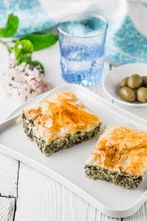 fillo: Greek pie spanakopita on the white plate with accessorizes vertical