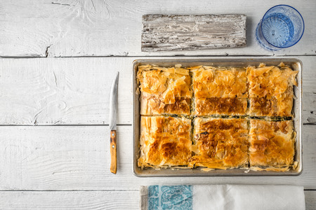 fillo: Greek pie spanakopita in the metal pan  with table ware horizontal