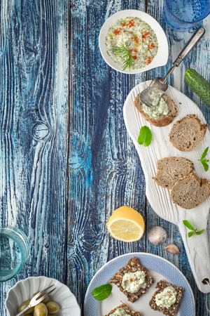 accessorize: Bread with tzatziki on the blue wooden table with accessorize vertical