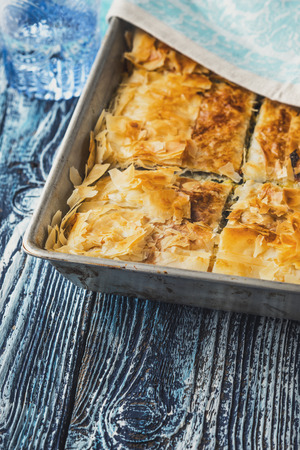 fillo: Greek pie spanakopita in the metal pan  on the blue wooden table vertical Stock Photo