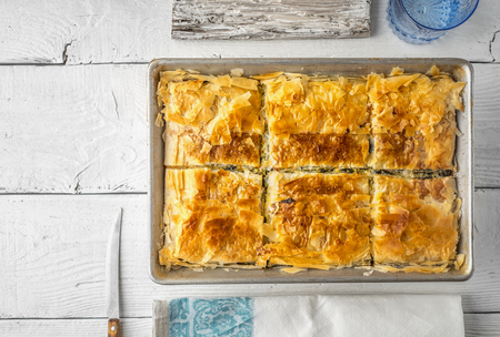 fillo: Greek pie spanakopita in the metal pan  with table ware top view Stock Photo