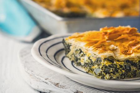 fillo: Greek pie spanakopita in the ceramic plate on the white  table  horizontal