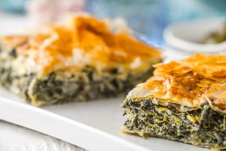 fillo: Greek pie spanakopita on the white plate with blurred accessorizes horizontal Stock Photo