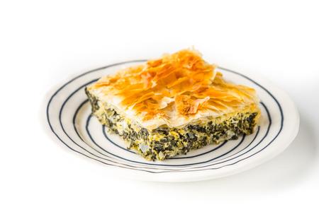 fillo: Piece of Greek pie spanakopita on the ceramic plate on the white background