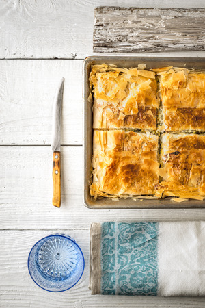 fillo: Greek pie spanakopita in the metal pan  with table ware vertical