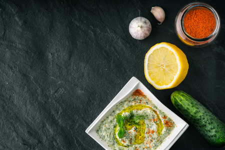 tzatziki: Tzatziki  on the  stone table with vegetables and seasoning top view