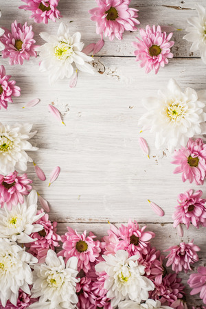 Frame of   pink  and white flower on the white wooden table vertical