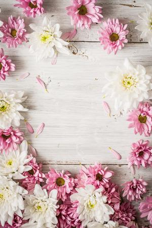 Quadro di fiori rosa e bianco sul tavolo di legno bianco verticale Archivio Fotografico - 62071261