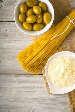 Spaghetti grezzi con le olive e formaggio sul verticale di legno bianco della tavola