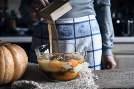 Woman Adding spices in the dough for pumpkin dump cake Stock Photo