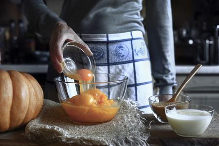 adding: Adding eggs in the pumpkin puree in the glass bowl Stock Photo