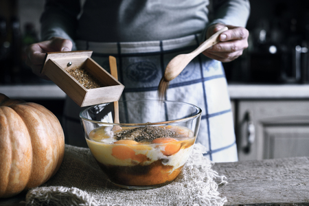 adding sugar: Woman Adding spices in the glass bowl with in the dough for pumpkin dump cake