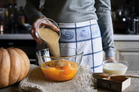 adding: Adding sugar in the dough for pumpkin dump cake horizontal